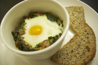 A supper best eaten standing: Baked eggs with kale, cream and mushrooms